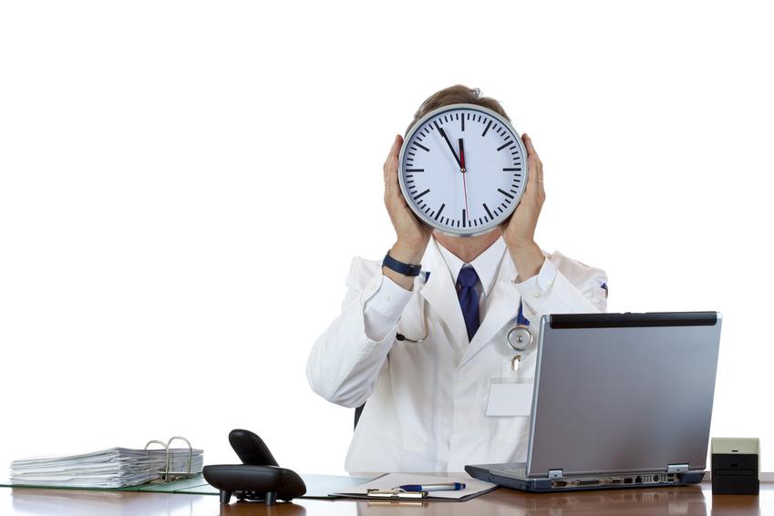 Gestresster Arzt hält Uhr vor Gesicht als Zeichen von Zeitdruck